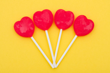 Red heart shaped lollipops on yellow background