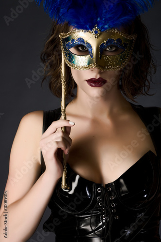 Beautiful young woman holding a carnival mask wearing catsuit