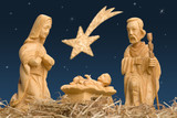 Wooden figures of Mary and Joseph watching baby Jesus