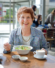 senior women having salad and coffee in a coffee shop