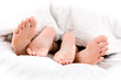 Vier Füße liegen übereinander zwischen einer Decke