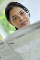 Jeune femme lisant un journal.
