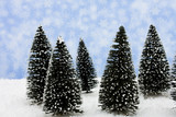 A group of evergreen trees on snow with snowflake background poster