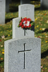 Three soldier tombstones with crosses and bouquet of flowers