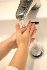 child washes hands by soap