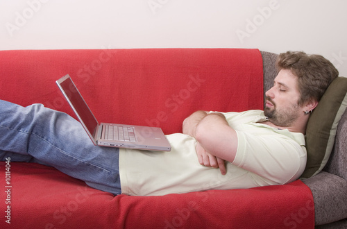 young man fall asleep while working on the laptop