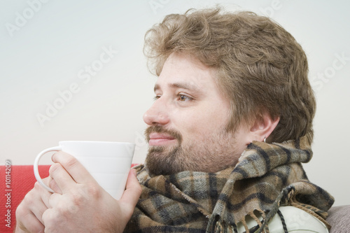 Handsome young man is getting warm drinking his coffee