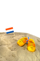 Dutch beach with wooden shoes and flag