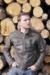 Mann mit Lederjacke lehnt an einem Holzstapel