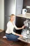 The blonde sits near to the open dishwasher on kitchen poster