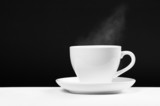 white cup with hot beverage over black background poster