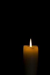 Lit candle on black background with copyspace