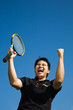 A happy asian tennis player in joy of winning