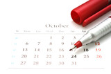 Red pen on a calendar of October. poster