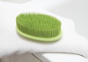 Green massage brush on white double towel