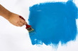 Painting the wall blue with a paint brush