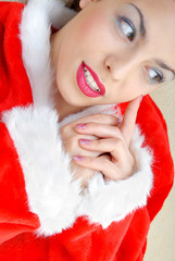 Thinking serene sexy woman in Santa Claus costume