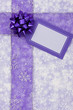 Purple ribbon and blank gift tag on snowflake background