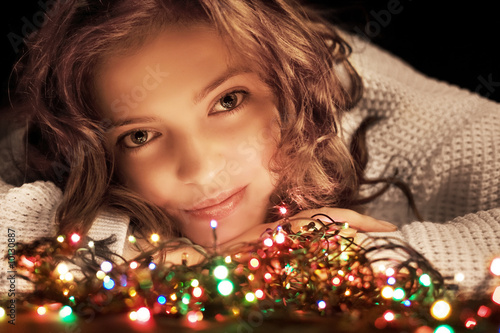 beauty woman with christmas garland over black