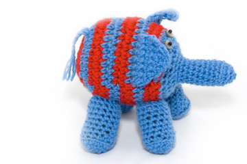 Knitted blue elephant with red stripes