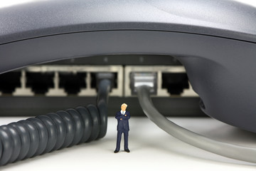 IP Telephony concept. Miniature businessman and phone equipment