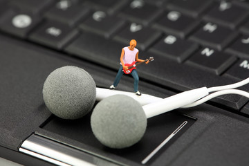 Miniature guitar player standing on ear buds on a laptop. MP3