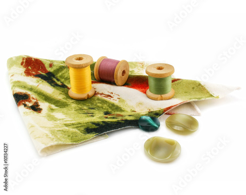 Piece of cloth, colored threads and buttons isolated