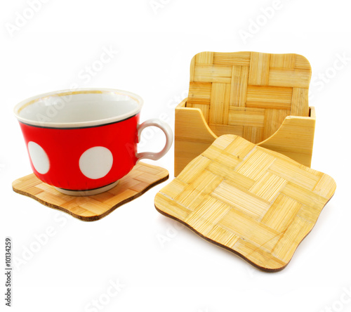 Colored cup and set of wooden trivets isolated