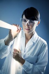 Italian woman holding neon stick in lab