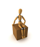 Wooden mannequin sitting on moving box over white poster