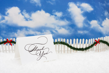 Thank you card sitting on snow with white fence and garland