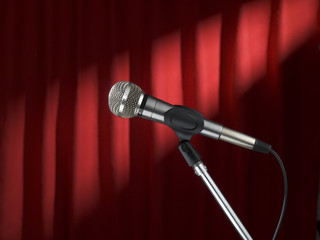 A microphone on stage over a red background.