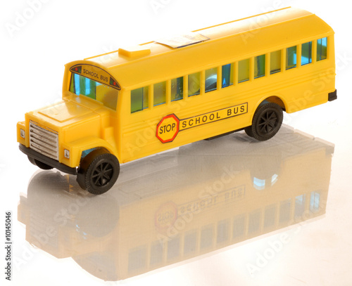 plastic yellow toy school bus on white background..