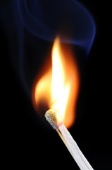 Burning fire of match on black background with blue smoke
