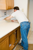 Contractor installing a new laminate kitchen counter top. poster