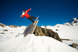 Snowboarder doing trick on wall ride, blue sky background poster