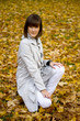 Young woman sits on autumn leaves. Focus on the face.