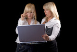 Two young businesswomen with laptop. Isolated on black poster