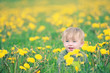 Cute small boy in green grass - he smiles and has fun