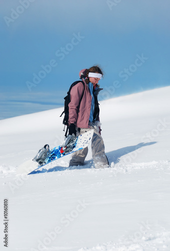 Young lady snowboarder walking