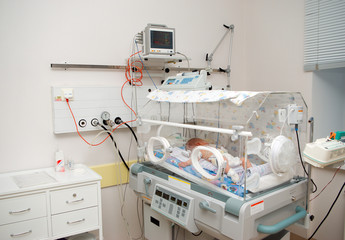 newborn baby sleeping in an incubator in hospital.