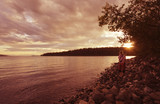 Young woman on lakeshore enjoying sunset , Canada poster