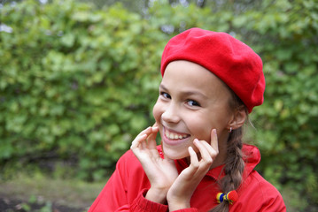 Cheerful preteen in red girl clasping hands on green background