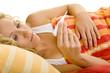 Blonde Frau im Bett schaut auf ein digitales Fieberthermometer