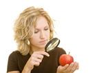 Fototapety Blonde Frau betrachtet einen roten Apfel unter einer Lupe