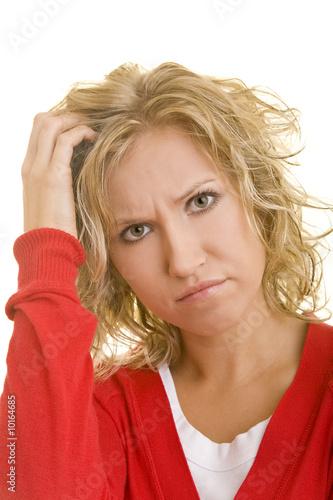 Blonde Frau kratzt sich nachdenklich am Kopf
