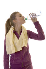 Young brunette girl drinink water after exercising
