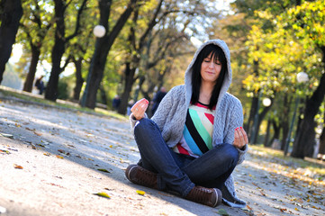 brunette Cute young woman  sitting outdoors in nature