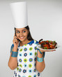 a smiling female chef talking on her cell phone