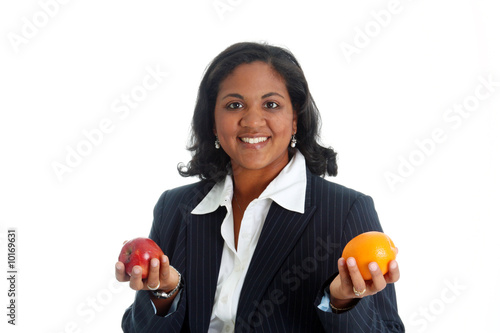 Woman comparing apples and oranges on a white background